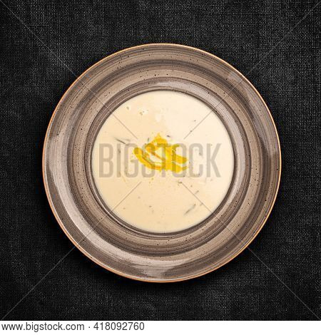 Flat Lay View Of Baked Potato Soup With Cheddar Cheese On Dark Background.