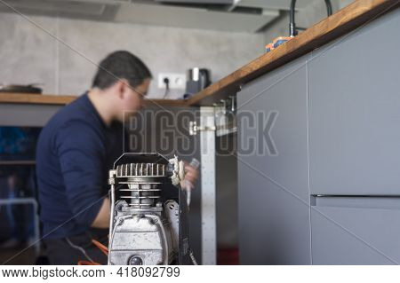 An Air Compressor In Focus And A Plumber At Work In The Blurred Background