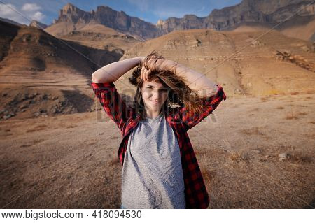 Happy Attractive Hipster Traveler Girl With Windy Hair And Smiling Against The Backdrop Of Sunny Mou