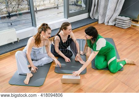 Three Sportive Girls Sit On Mats In Fitness Studio During Online Yoga Exercises Workout Training Tut