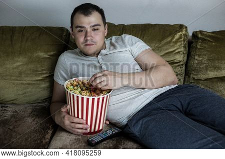 Fat Lazy Man Lying On The Couch Watching Tv And Eating Popcorn. A Man Falls Asleep In Front Of The T