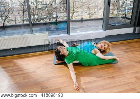 Two Female Friends Sit In Lotus Yoga Pose Back To Back, Group Exercise Workout Training Indoors, Hea