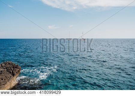 Two White Sailboats Are Sailing On The Open Sea On A Sunny Bright Day. View From The Rocky Shore