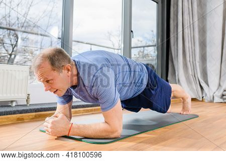Middle Age Fit Sportsman Sitting In Yoga Lotus Pose Near Panoramic Window Indoors, Healthy Pension A