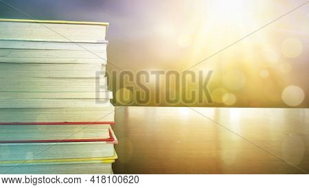 Education Learning Concept: Opening Book On Reading Desk And Aisle Of Bookshelves In Natural Backgro