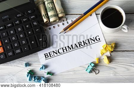 Benchmarking - Word On A White Sheet Against The Background Of A Calculator, Banknotes, Cups Of Coff
