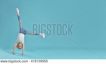Joyful Little Girl Child Stands Upside Down On Hands.
