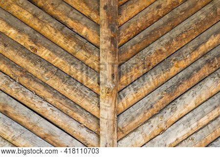 A Cottage Exterior Wall Made Of Wooden Logs With Texture And Wood Knots. Debarked Barn Or Rural Cabi