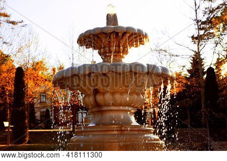 Marble Fountain With Splashing Water . Outdoor Fountain With Base Bow . Autumn In The City Park
