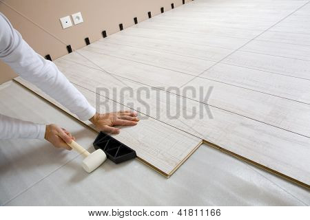 Worker laying a floor with laminated flooring boards
