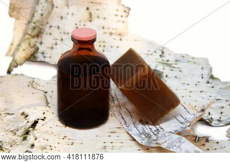 Liquid Tar In A Bottle And A Piece Of Tar Soap On Birch Bark Background