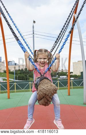 Cute Caucasian Child Girl Swinging On A Swing On A Children's Playground.
