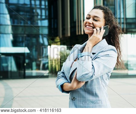 A young african woman dressed in business style against the background of a business center is holding a mobile phone