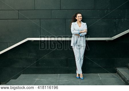 Business, people and lifestyle concept: young african woman in a stylish blue suit stands near the stairs.