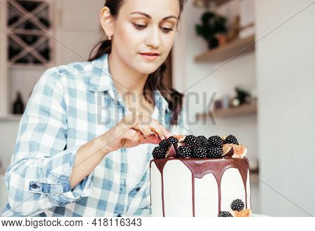 Pastry chef decorates the cake with fresh berries and figs.