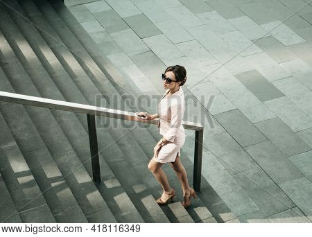 woman dressed in business style next to the stairs, business and career concept