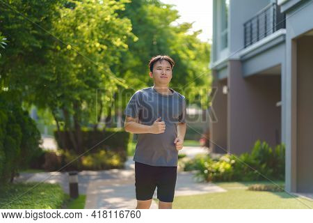 Asian Man Are Jogging In The Neighborhood For Daily Health And Well Being, Both Physical And Mental