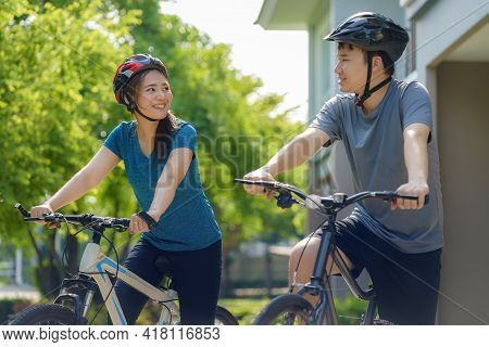 Asian Couple Wearing A Helmet While Preparing For A Bike Ride Around Her Neighborhood For Daily Heal