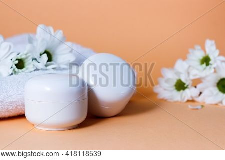 Cream In White Tubes Or Bottles On A Beige Background With Flowers Of White Chryzantemy. Cosmetic Pr