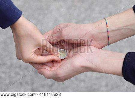Hand Of The Young Woman While Giving Alms With A Coin To The Poor Child
