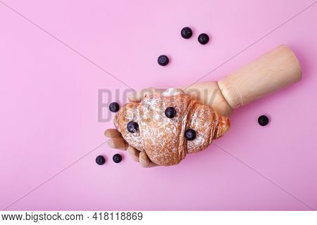 Wooden Hand Showing Baked Croissant With Raw Blueberriy On Pink Background