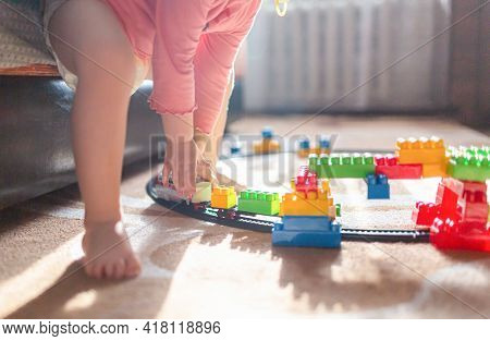Ttoddler Child Girl In A Diaper Plays In Room With Train Toy