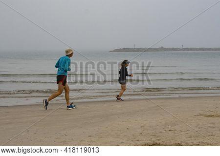 Tel Aviv, Israel - April 16th, 2021: A Couple Of Joggers On The Tel Aviv, Israel, Beach On A Foggy M