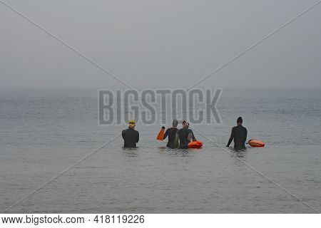 A Group Of Open Water Swimmers In The Mediterranean Sea On A Chilly, Hazy Day.