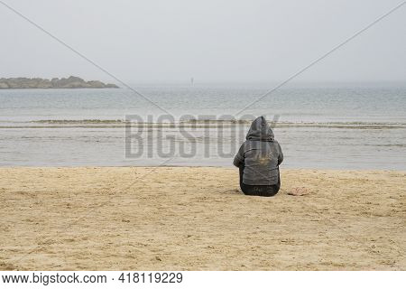 A Person Seating On A Deserted Beach On A Hazy Morning, Facing The Mist Covered Sea.