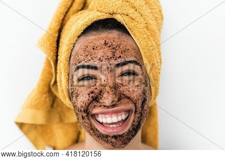 Young Smiling Woman Applying Coffee Scrub Mask On Face - Happy Girl Having Skin Care Spa Day At Home