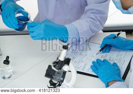 Team Of Medical Research Scientists Or Researcher In Lab Coat Testing Their Experimental In Modern L