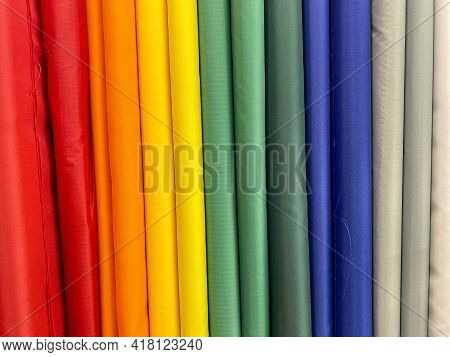 Bolts Of Colored Fabric Lined Up Like The Rainbow - In A Fabric Store.
