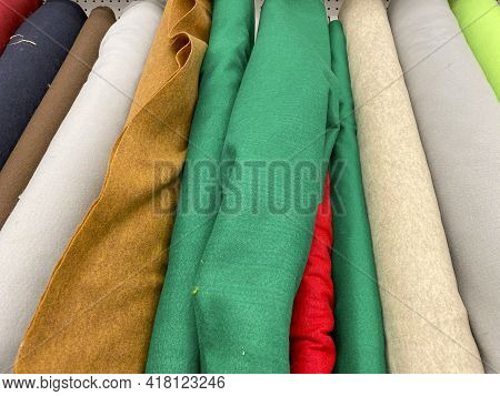 Colorful Bolts Of Fabric With Different Patterns In A Fabric Store