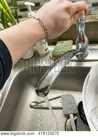 Person Turning On A Sink To Wash Dishes At Home