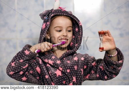 A Little Cheerful Girl In A Hooded Robe Brushes Her Teeth With Toothpaste With An Hourglass Timer. P