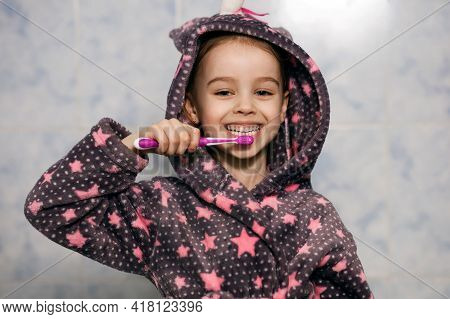 Cheerful Little Girl In A Hooded Robe Brushes Her Teeth With Toothpaste And Smiles. Parents Teach Th