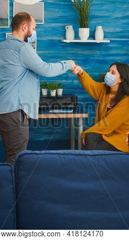 Man Greeting Friends Coming At Party Wearing Protective Mask