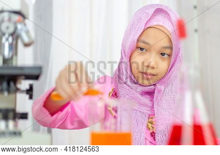 Muslim Girl In Elementary School In A Science Lab Experiment, Islamic Kindergarten Students Are Play