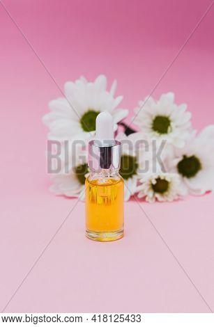 Small Bottle Of Cosmetic Oil For Cuticle With Flowers. Dropper Glass Bottle. Cosmetic Pipette On Pin