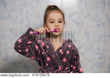 A Little Girl In A Robe Brushes Her Teeth With Toothpaste. Parents Teach Their Child To Brush Their