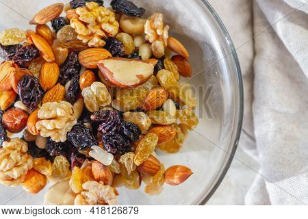 A Plate With A Mixture Of Nuts And Dried Fruits, Raisins, Walnuts, Hazelnuts, Almonds, Cashews