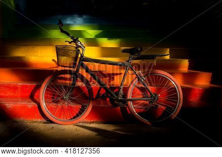 Black Bicycle Parked On Colored Stairs. Stairs With Rainbow Colors Illuminated By Sunlight