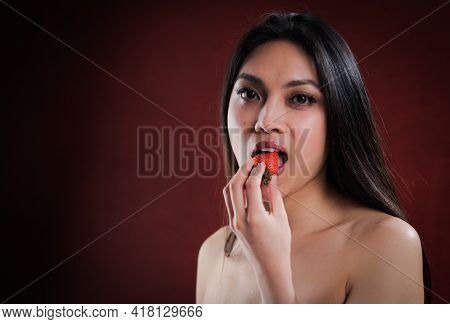 Young Pretty Woman Bites Into A Strawberry - Studio Photography