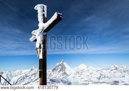 Cross Under The Snow On Klein Matterhorn. Matterhorn In The Background