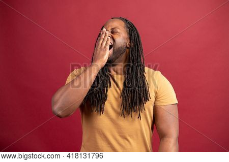 Sleepy African-american Guy Yawns And Feels Bored Isolated On Red Background, Tired Black Man Feels
