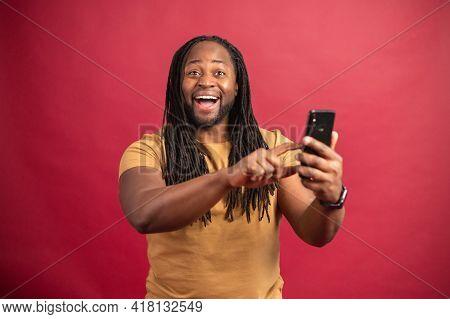 Surprised Smiling Dark Skinned Man With Long Dreadlocks Holding Phone, Amazed African Guy Reading Go