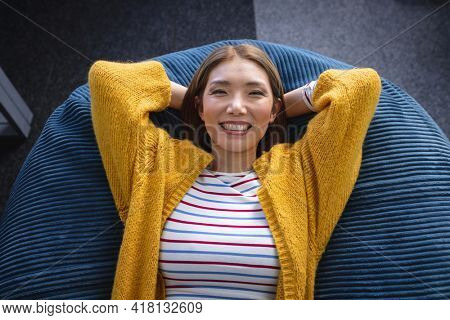 Happy mixed race businesswoman chilling in office relaxing space lying in beanbag smiling. independent creative design business.