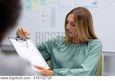 Caucasian businesswoman in discussion at work pointing at document. working person in a modern office