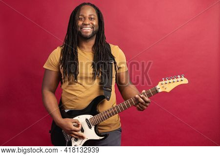Smiling Energetic And Enthusiastic Young African American Male Musician With Dreadlocks Playing Elec