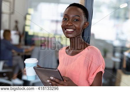 Portrait of happy african american businesswoman holding cup of coffee and digital tablet. business in a modern office.